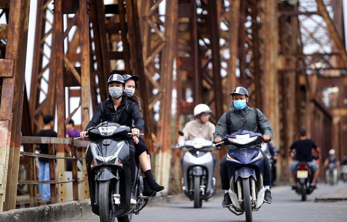 Người dân với trang phục áo ấm đi trên cầu Long Biên (Hà Nội). (Ảnh: Danh Lam/TTXVN)