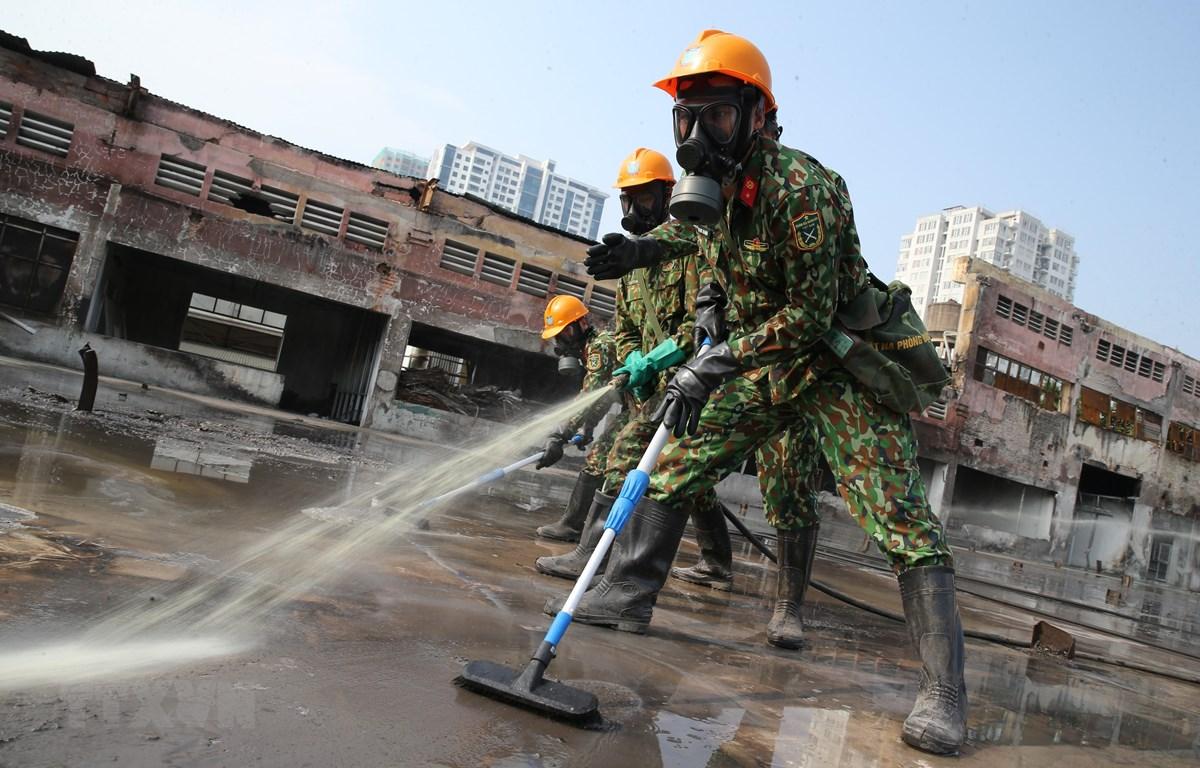Lực lượng Binh chủng Hoá học phun hóa chất tẩy độc mặt nền nhà xưởng của Công ty Rạng Đông, ngày 5/10. (Ảnh: Dương Giang/TTXVN)