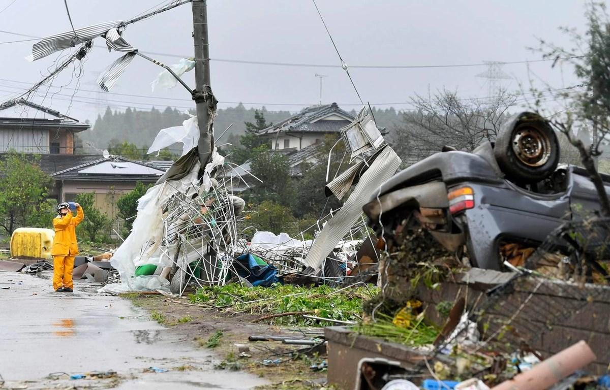 Một công nhân đứng giữa chụp ảnh những mảnh vỡ sau cơn bão Hagibis quét qua Ichihara, Chiba, gần Tokyo. (Nguồn: AP)