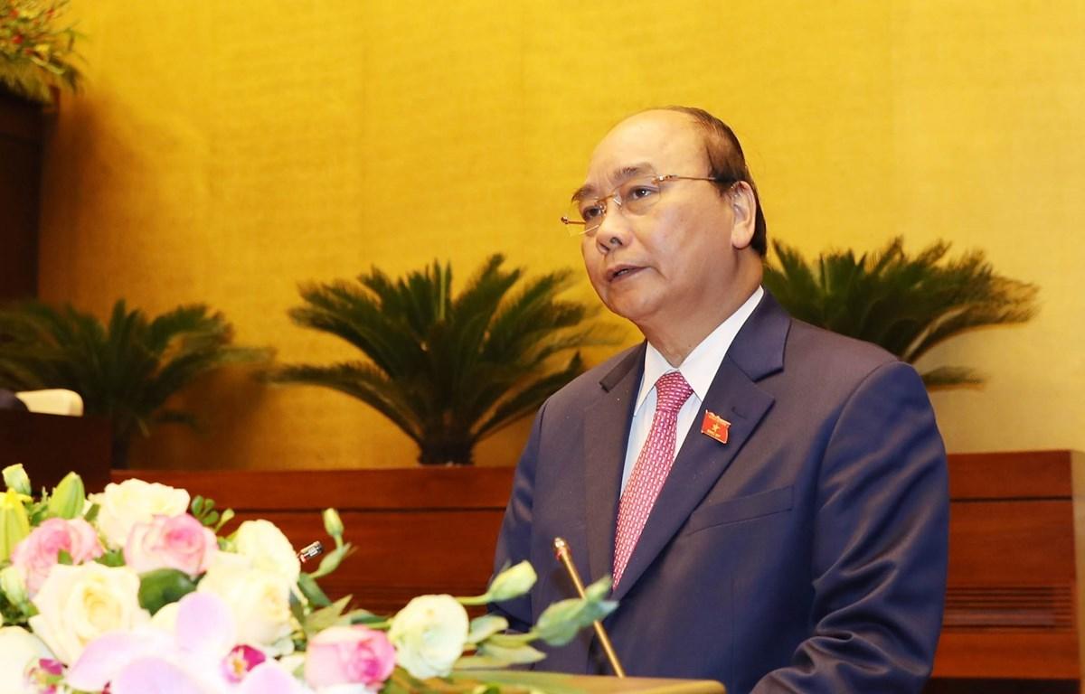 Thủ tướng Nguyễn Xuân Phúc đọc báo cáo của Chính phủ. (Ảnh: Trọng Đức/TTXVN)