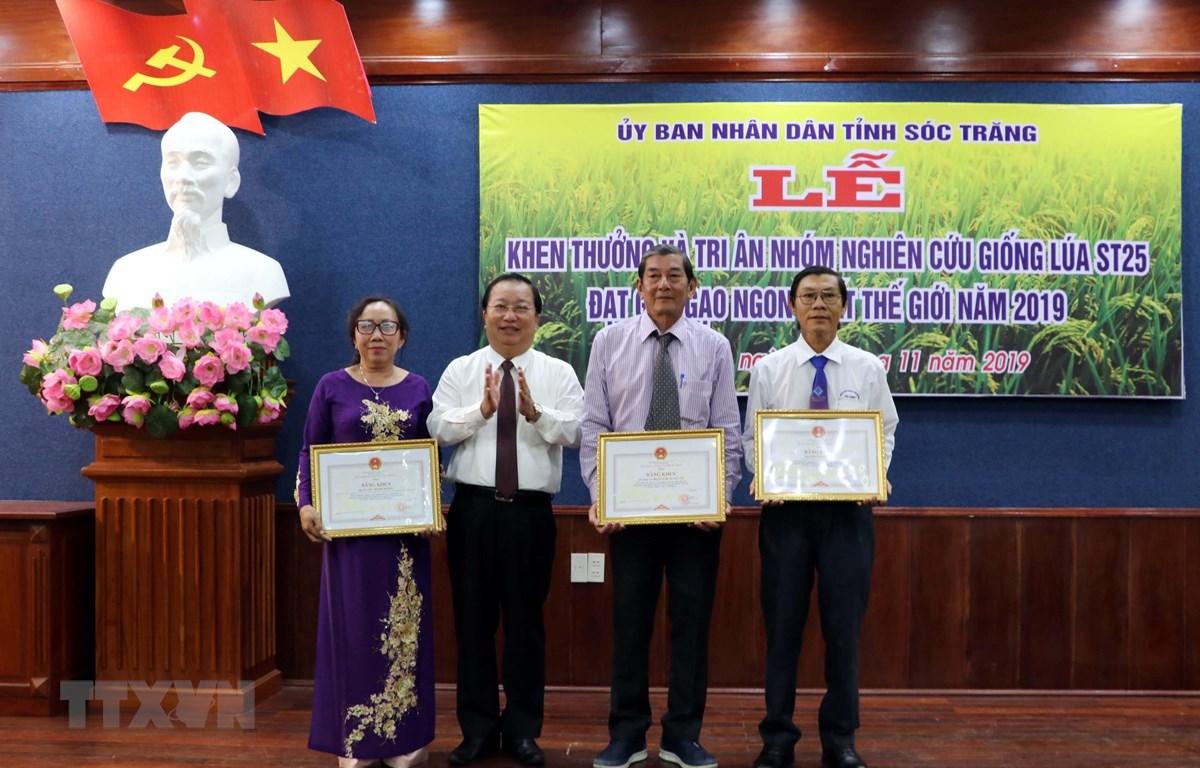 Chủ tịch Ủy ban Nhân dân tỉnh Sóc Trăng tặng bằng khen cho nhóm lai tạo giống lúa. Ảnh: Trung Hiếu/TTXVN)