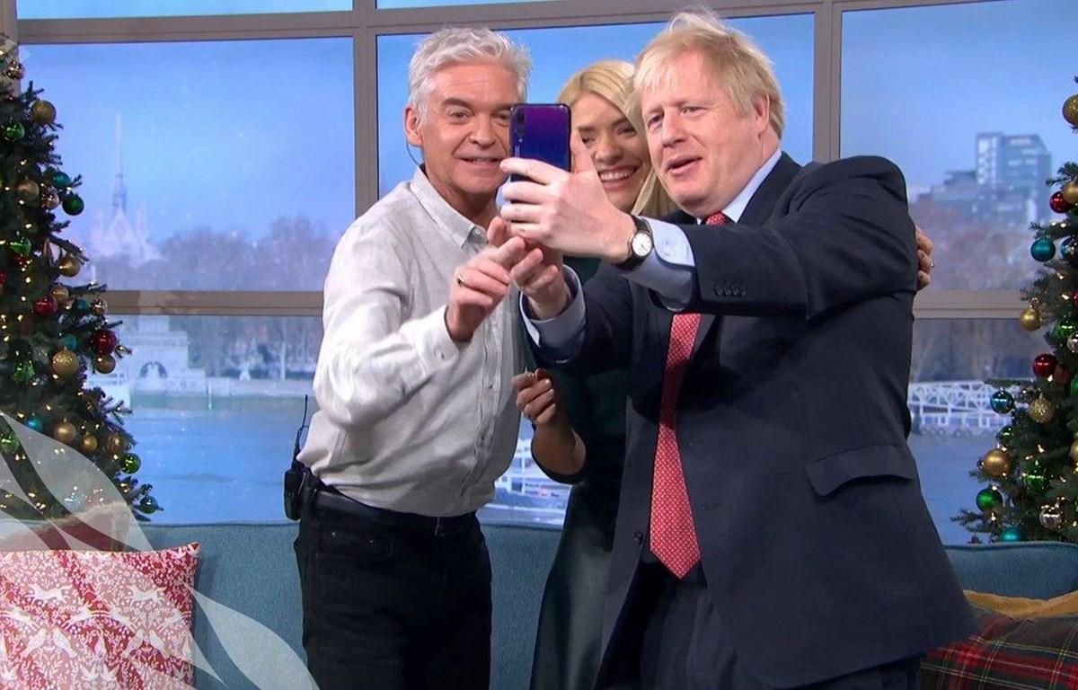 Hình ảnh Thủ tướng Johnson dùng điện thoại Huawei chụp ảnh tự sướng kỷ niệm với hai người dẫn chương trình. (Nguồn: https://twitter.com/johnestevens)