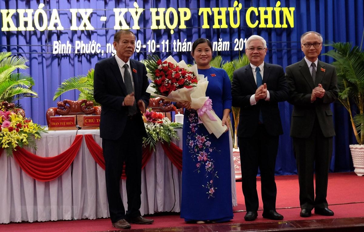 Lãnh đạo tỉnh Bình Phước tặng hoa chúc mừng bà Trần Tuệ Hiền. (Ảnh: Dương Chí Tưởng/TTXVN)