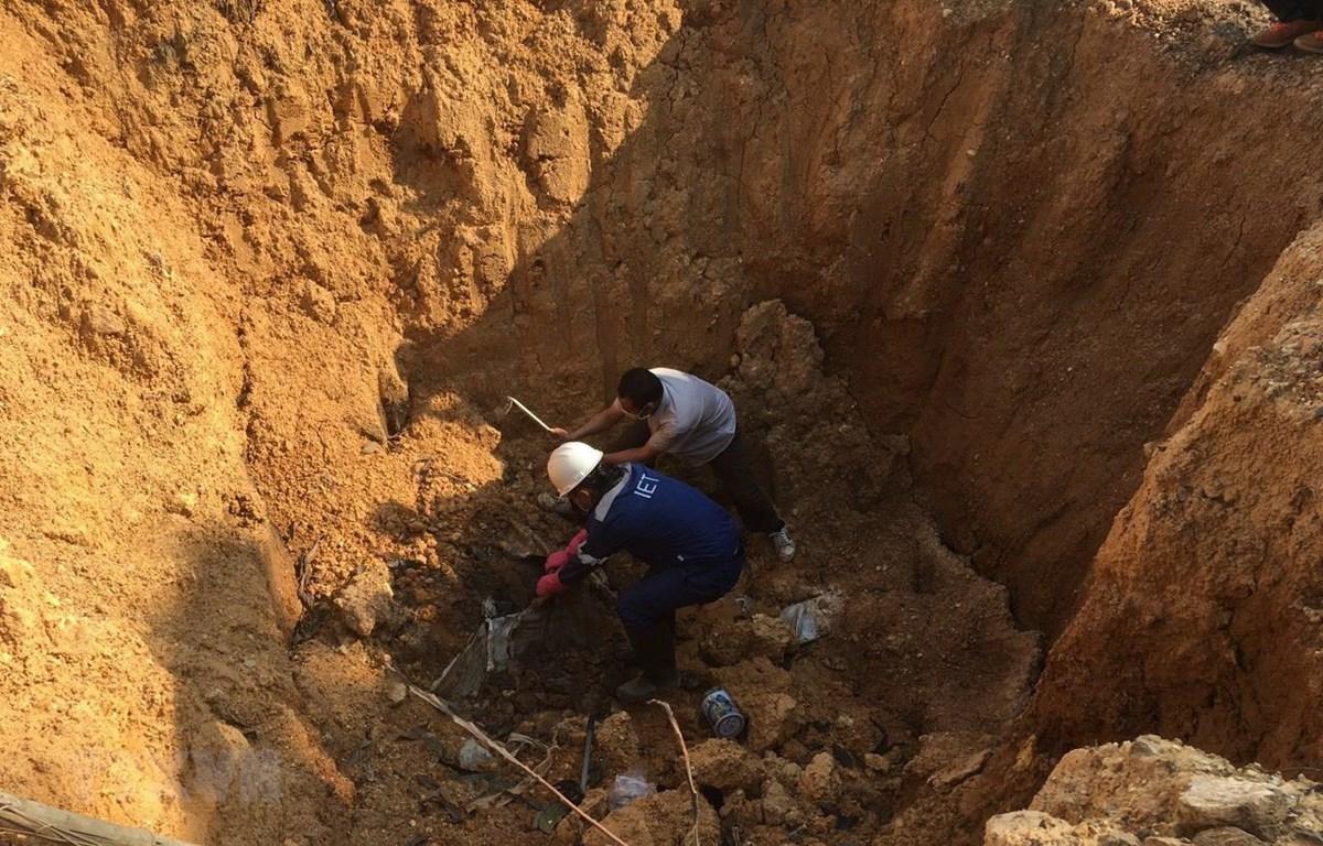 Hố chôn lấp chất thải đổ trộm có kích thước 2mx2m, chưa xác định được độ sâu, có chứa các chất màu trắng giống ximăng, có mùi hắc. (Ảnh: Mạnh Khánh/TTXVN)