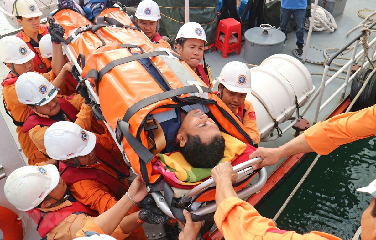 Thuyền viên Syaiful Chandra được đội cứu nạn đưa lên bờ để chuyển đến bệnh viện tiếp tục điều trị. (Ảnh: Nguyễn Dũng/TTXVN)