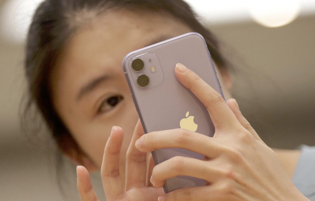 Một người tiêu dùng Trung Quốc sử dụng iPhone 11. (Nguồn: Reuters)