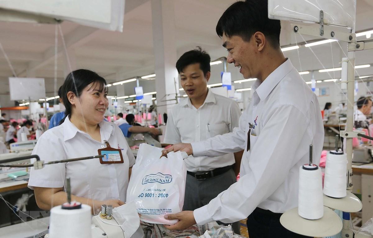 Ông Lê Văn Hải, Phó Tổng Giám đốc Công ty Cổ phần Thương mại xuất nhập khẩu May Phương Nam, quận Gò Vấp, Thành phố Hồ Chí Minh (giữa) cùng Chủ tịch Công đoàn Công ty Trần Phú Vinh (phải) tặng quà Tết Dương lịch 2020 cho công nhân lao động có hoàn cảnh khó