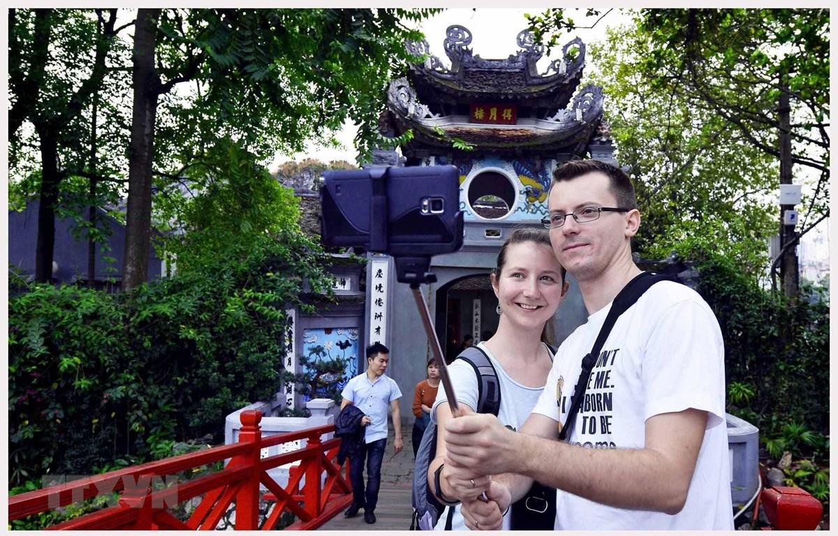 Khách du lịch quốc tế tham quan, chụp ảnh kỷ niệm tại đền Ngọc Sơn (Hà Nội). (Ảnh: Thanh Hà/TTXVN)