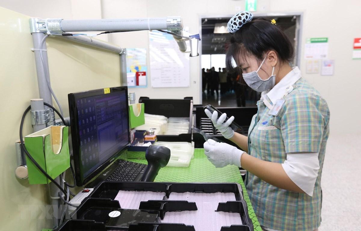 Người lao động tại Công ty trách nhiệm hữu hạn Samsung Electronics Việt Nam đeo khẩu trang và sử dụng các biện pháp phòng chống dịch viên đường hô hấp cấp COVID-19. (Ảnh: Anh Tuấn/TTXVN)