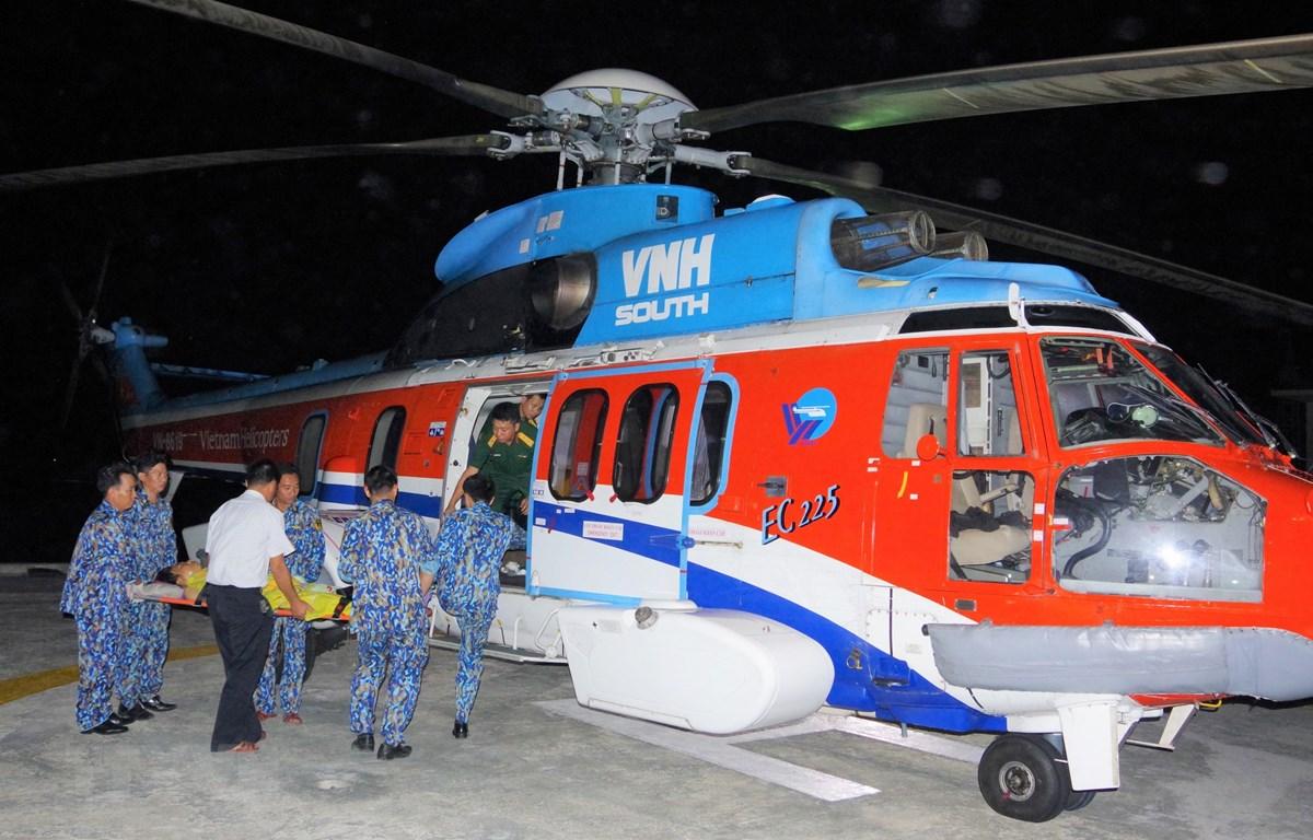 Bệnh nhân được vận chuyển lên trực thăng đưa về đất liền cấp cứu. (Nguồn: TTXVN phát)