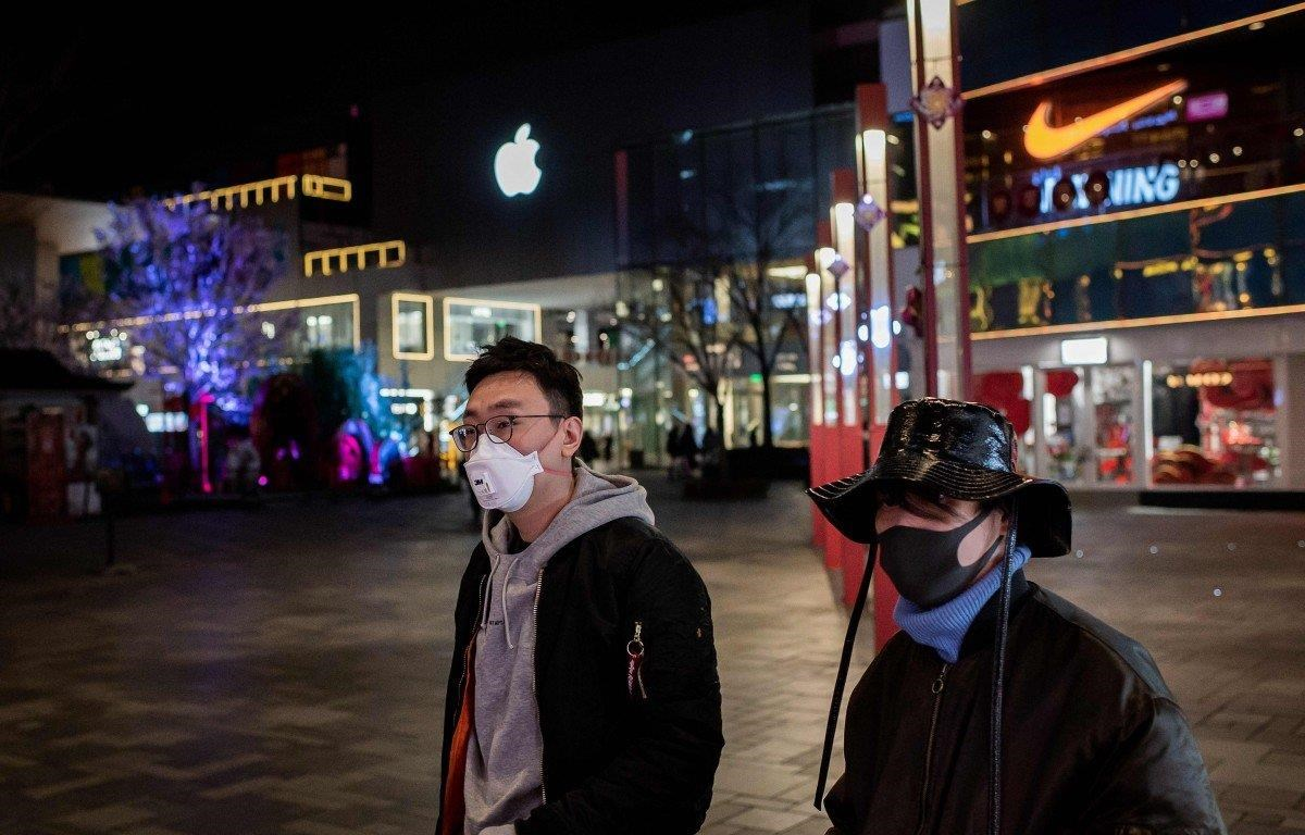 Người dân đeo khẩu trang đi ngang qua một cửa hàng Apple bên ngoài một trung tâm mua sắm vắng vẻ ở Bắc Kinh vào ngày 24/2. (Nguồn: AFP)