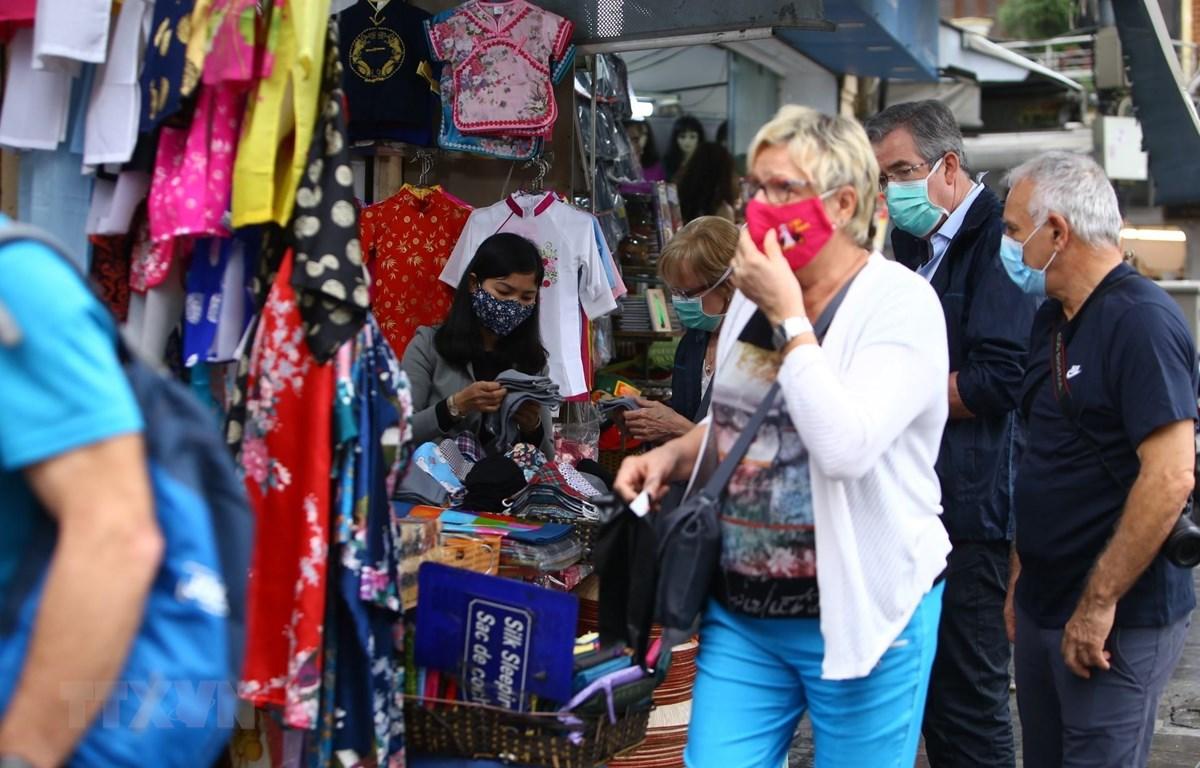 Khách du lịch nước ngoài đeo khẩu trang khi tham quan, mua sắm ở Việt Nam trong thời kỳ dịch COVID-19. (Ảnh: Minh Quyết/TTXVN)