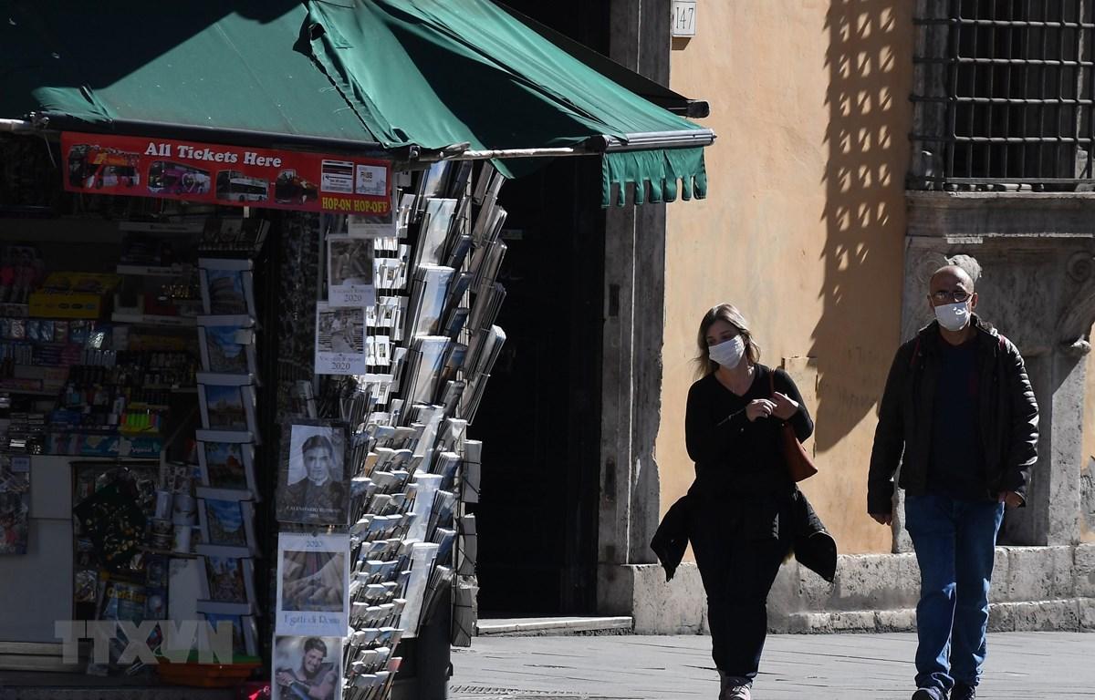 Người dân đeo khẩu trang để phòng tránh lây nhiễm COVID-19 tại Rome, Italy, ngày 12/3/2020. (Nguồn: THX/ TTXVN)