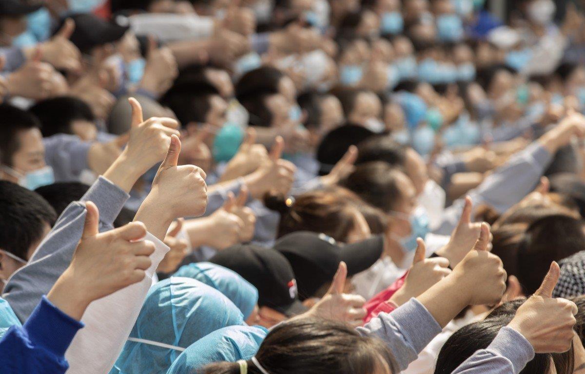Nhân viên y tế từ Hà Nam đưa ngón tay cái lên Vũ Hán trước khi rời thành phố vào thứ Năm 19/3. (Nguồn: Tân Hoa Xã)
