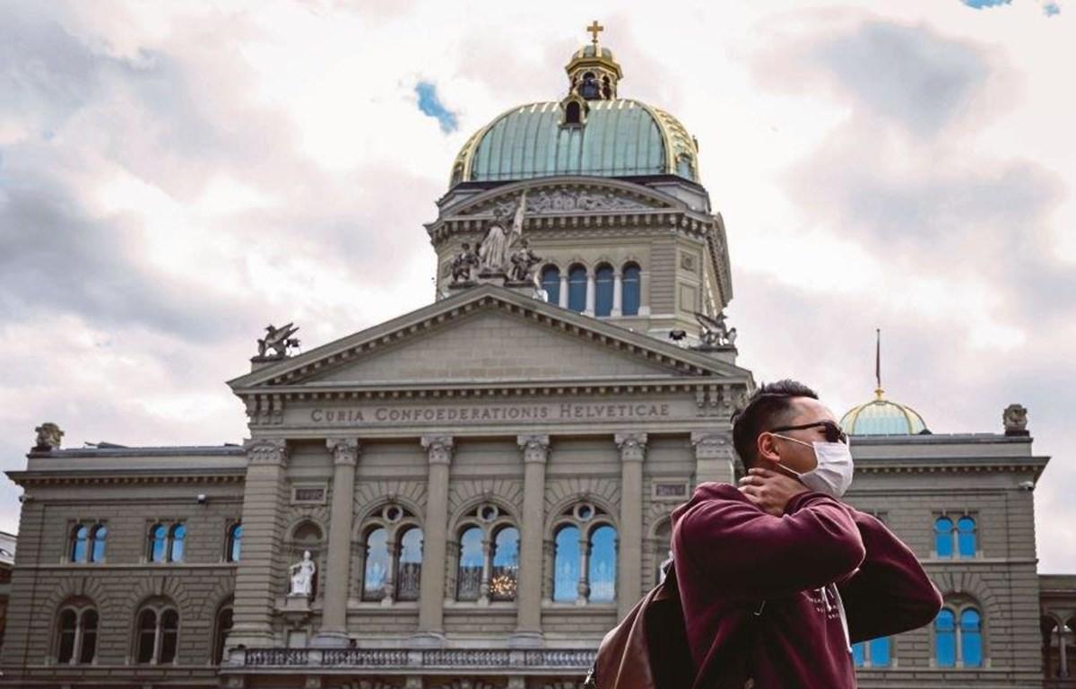 Một khách du lịch đeo khẩu trang được nhìn thấy trước Tòa nhà Quốc hội Thụy Sĩ vào ngày 13/3/2020, tại Bern. (Nguồn: AFP)
