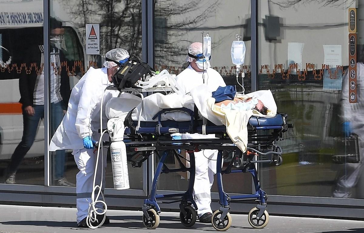 Nhân viên y tế chuyển bệnh nhân nhiễm COVID-19 tới bệnh viện ở Strasbourg, Pháp, ngày 16/3/2020. (Nguồn: AFP/TTXVN)