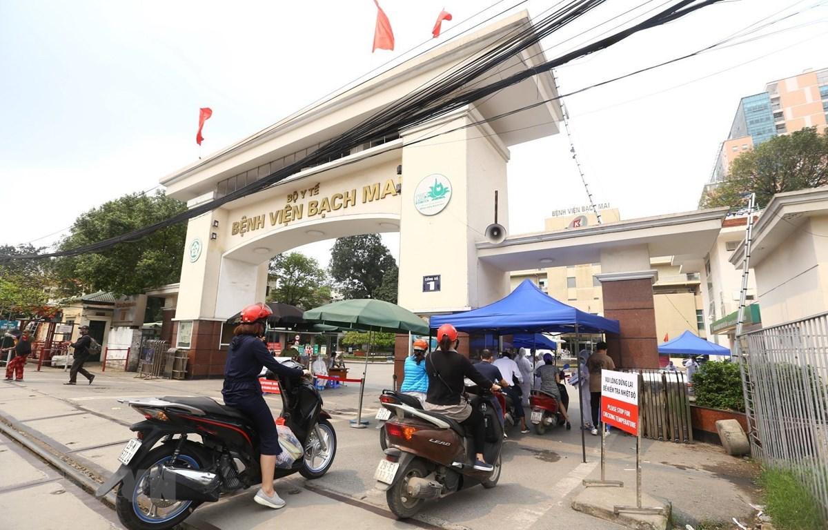 Tại cổng số 1 Bệnh viện Bạch Mai mọi hoạt động vẫn bình thường trong ngày 26/3, người dân khi vào cổng sẽ được đo kiểm tra thân nhiệt và sát khuẩn tay. (Ảnh: Minh Quyết/TTXVN)