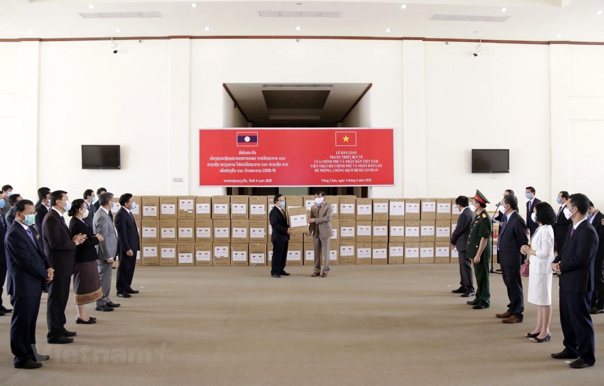 Quang cảnh lễ bàn giao hàng viện trợ của Chính phủ Việt Nam cho Chính phủ Lào để phòng chống dịch COVID-19. (Ảnh: Phạm Kiên/Vietnam+)