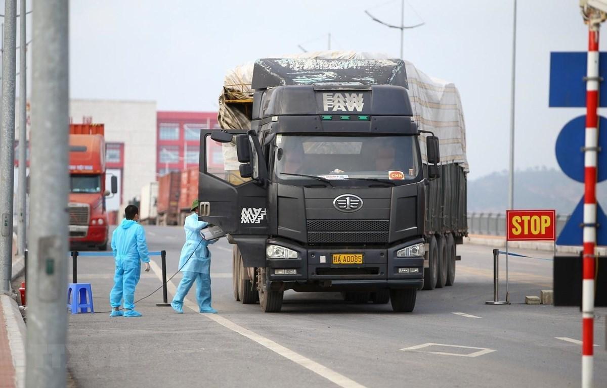 Cán bộ y tế tiến hành phun khử khuẩn buồng lái của xe nhập khẩu qua cầu Bắc Luân 2 - cửa khẩu quốc tế Móng Cái. (Ảnh: Minh Quyết/TTXVN)