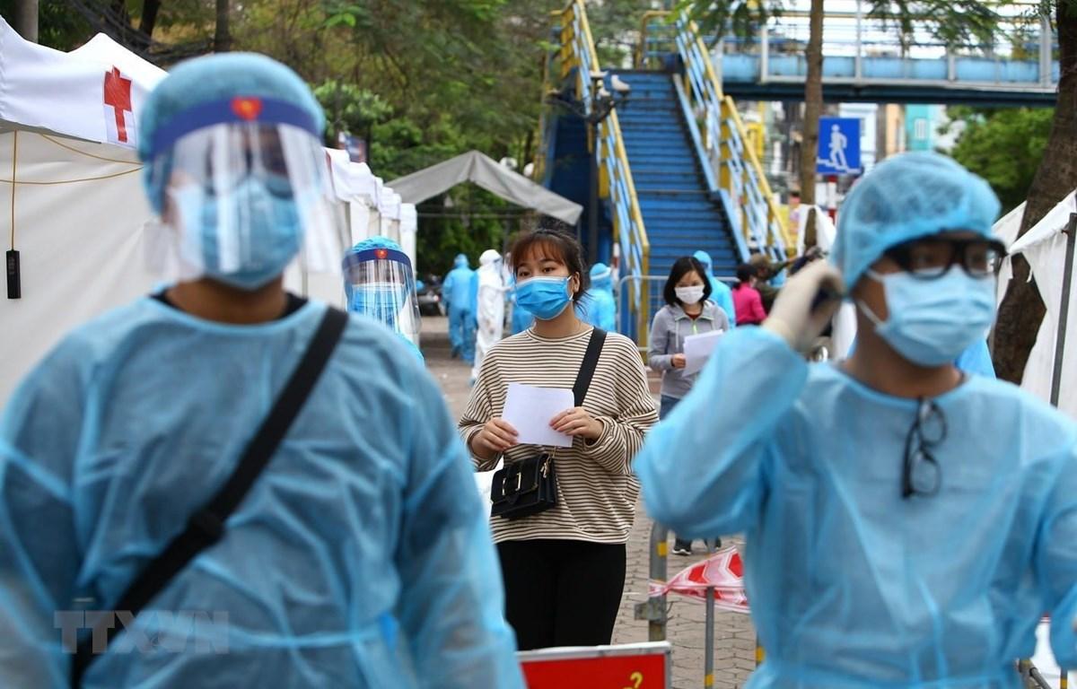 Nhân viên y tế Hà Nội được trang bị đầy đủ quần áo bảo hộ theo đúng quy định phục vụ trạm di động lấy mẫu xét nghiệm. (Ảnh: Minh Quyết/TTXVN)