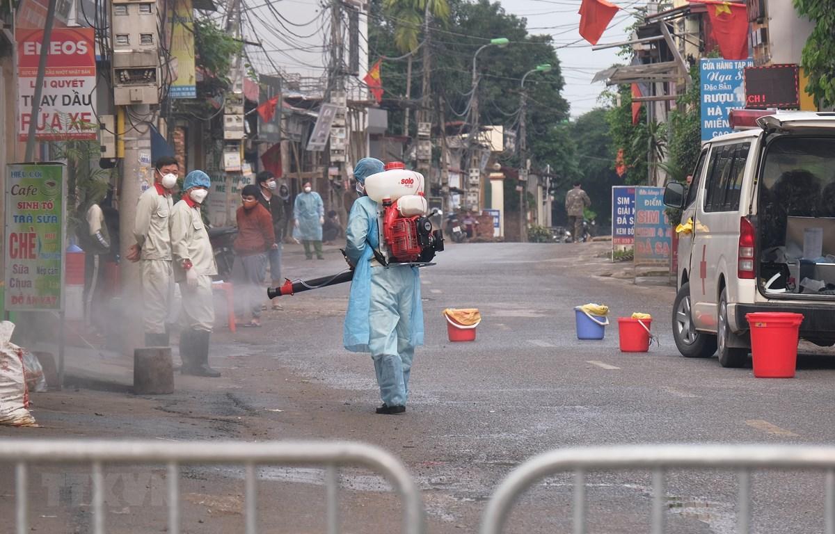 Lực lượng chức năng phun khử khuẩn tại thôn Hạ Lôi (Mê Linh). (Ảnh: Phạm Hùng/TTXVN phát)