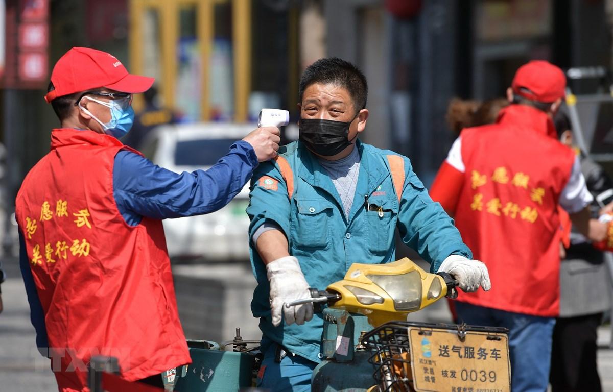 Tình nguyện viên kiểm tra thân nhiệt của người dân tại Vũ Hán, tỉnh Hồ Bắc, Trung Quốc ngày 15/4/2020. (Nguồn: THX/ TTXVN)
