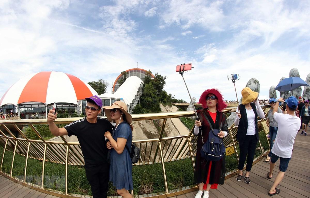 Khách du lịch chụp ảnh tại Cầu Vàng ở Khu du lịch Bà Nà Hills (Đà Nẵng). (Ảnh: Trần Lê Lâm/TTXVN)