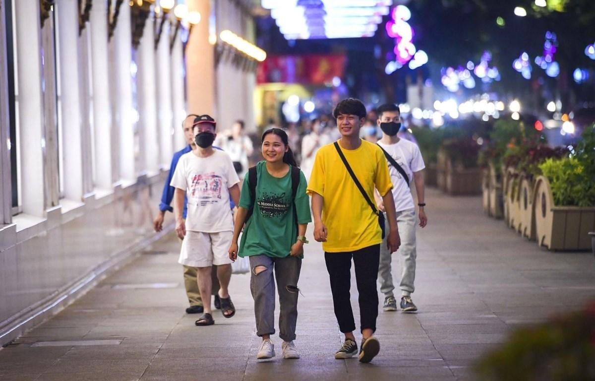 Các bạn trẻ thích thú với không khí trên phố đi bộ hồ Hoàn Kiếm ngày hoạt động trở lại sau thời gian tạm dừng hoạt động vì COVID-19. (Ảnh: Thành Đạt/TTXVN)
