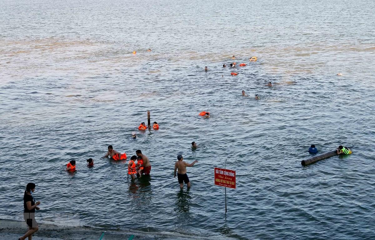 Bãi tắm tự phát hạ nguồn sông Lam đoạn qua địa bàn phường Bến Thủy, thành phố Vinh (Nghệ An) trở thành nơi tắm mát, giải nhiệt cho người dân thành phố Vinh. (Ảnh: Tá Chuyên/TTXVN)