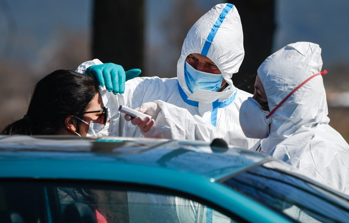 Nhân viên y tế kiểm tra thân nhiệt người dân nhằm ngăn dịch COVID-19 lây lan tại trạm kiểm tra ở khu nghỉ dưỡng Bansko, Bulgaria ngày 18/3/2020. (Nguồn: AFP/TTXVN)