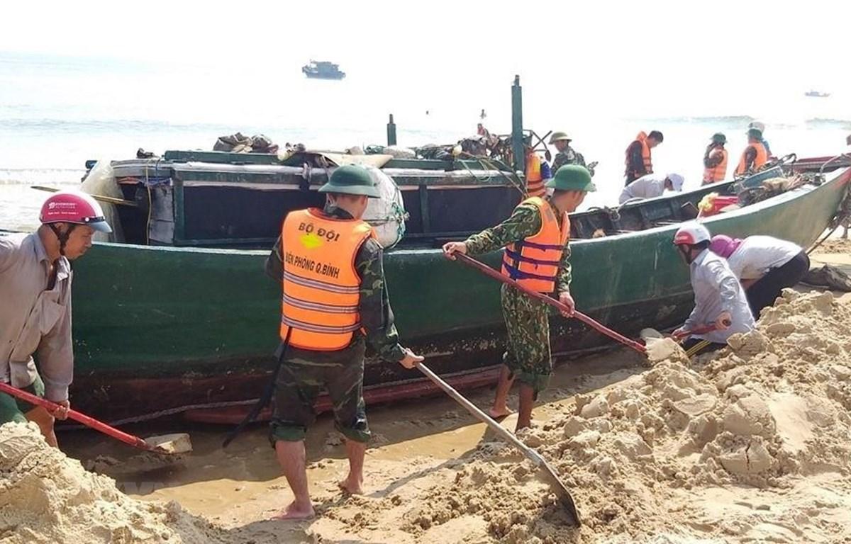 Cán bộ, chiến sĩ bộ đội biên phòng cùng nhân dân địa phương hỗ trợ giải cứu tàu cá gặp nạn. (Ảnh: Võ Dung/TTXVN)