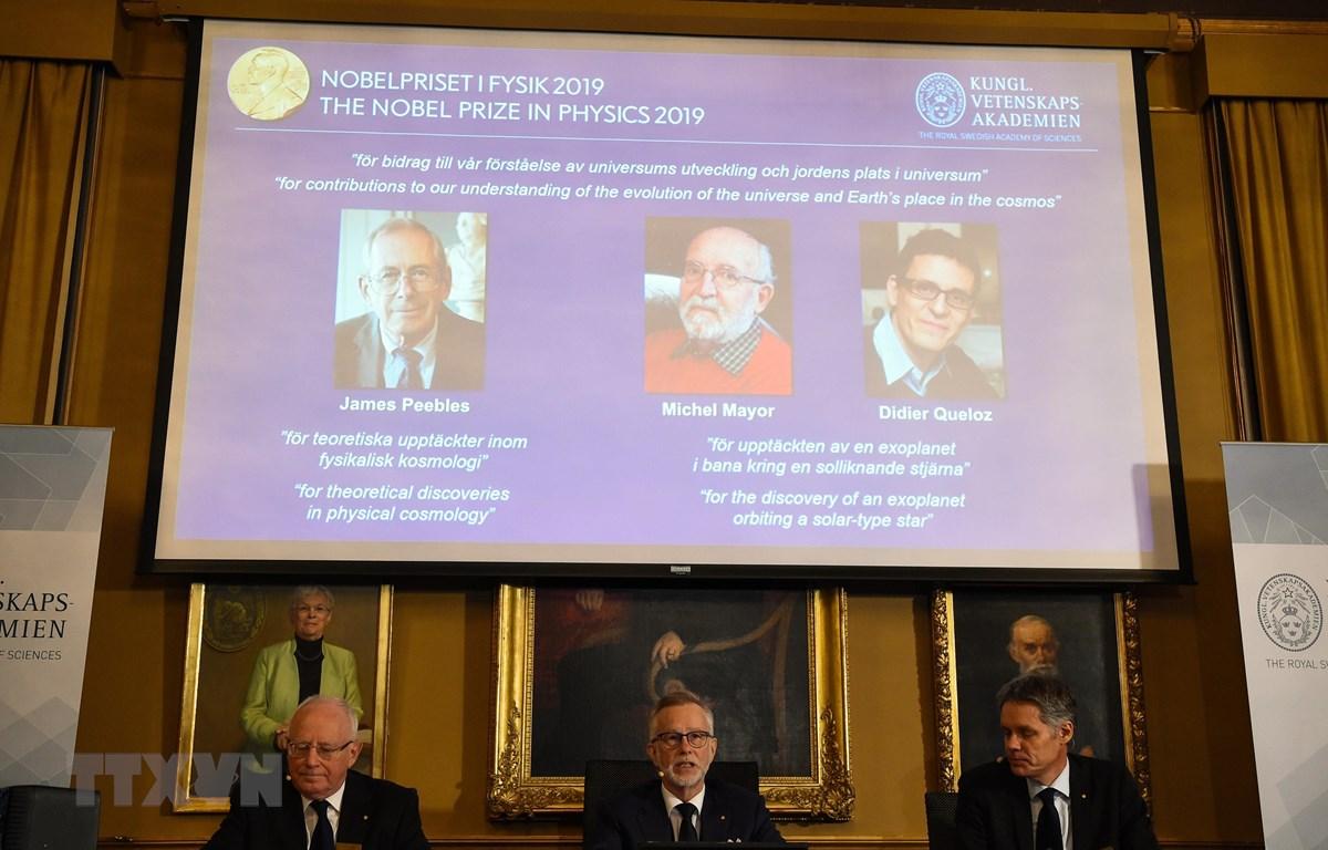 Ba nhà khoa học đoạt giải Nobel Vật lý 2019 (phía trên màn hình, từ trái sang): James Peebles, Michel Mayor và Didier Queloz được xướng danh tại Viện Khoa học Hoàng gia Thụy Điển Karolinska ở Stockholm ngày 8/10/2019. (Nguồn: AFP/TTXVN)
