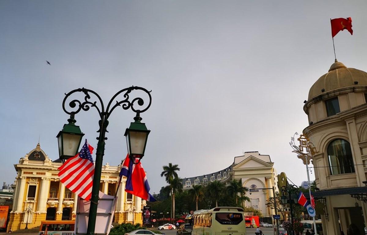 Cờ Mỹ và cờ Triều Tiên, bên dưới là biểu tượng hai bàn tay bắt chặt vào nhau thể hiện tinh thần của cuộc gặp lớn, được treo trên tuyến phố Tràng Tiền, trước khu vực Quảng trường 19/8 - Nhà hát Lớn - Khách sạn Hilton Opera, quận Hoàn Kiếm. (Ảnh: Thành Đạt/
