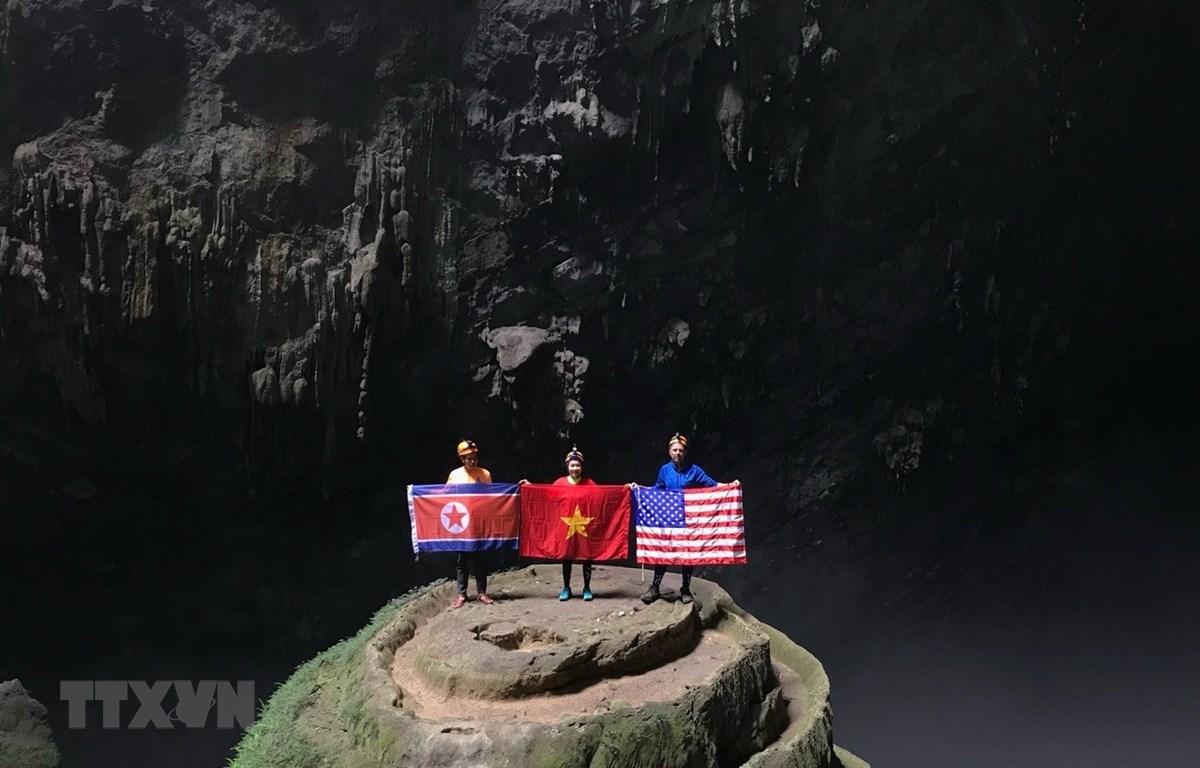 Khách du lịch khám phá hang động chụp ảnh cùng với 3 lá quốc kỳ Mỹ-Triều Tiên-Việt Nam tại hang Én, tỉnh Quảng Bình. (Ảnh: TTXVN phát)