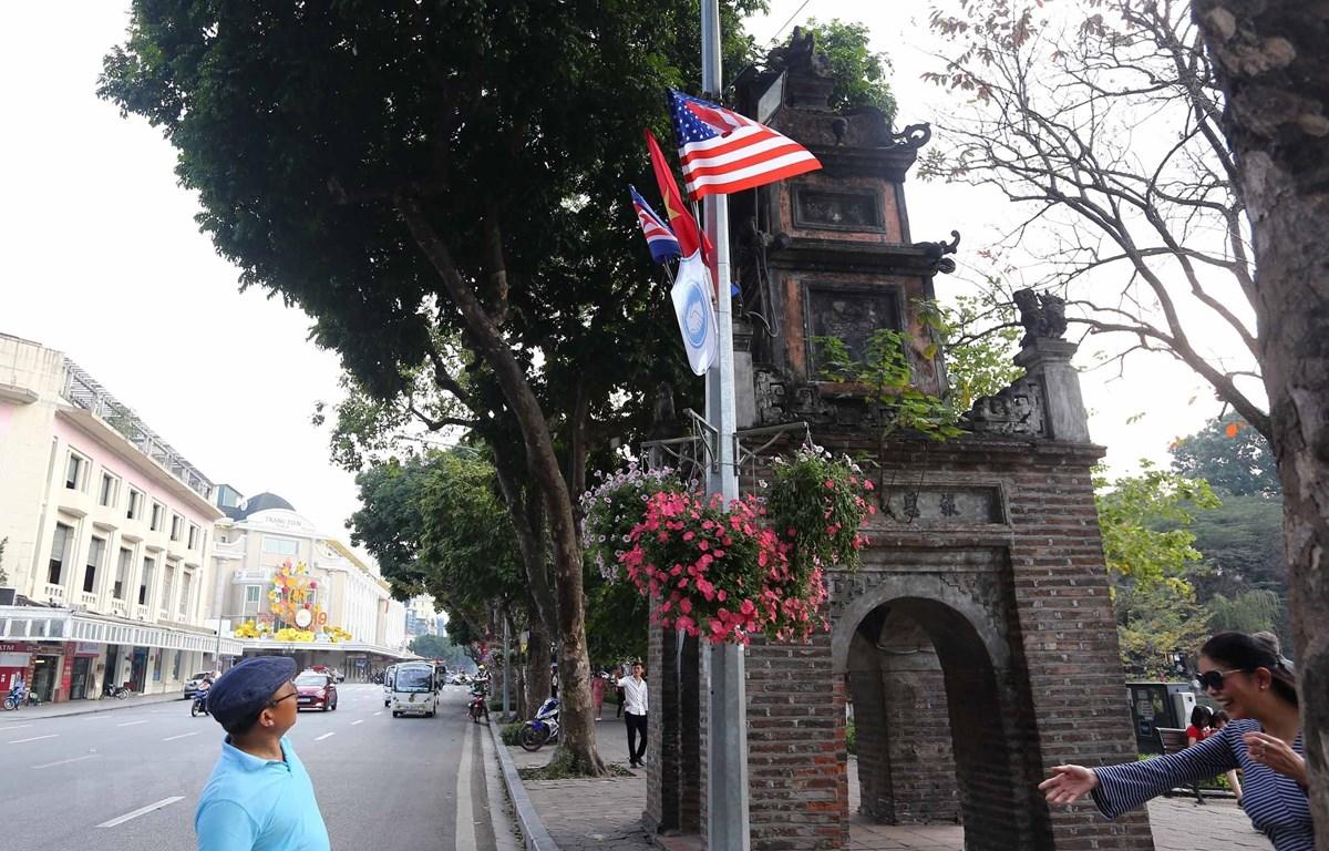 Cờ Mỹ, cờ Triều Tiên và cờ Việt Nam, bên dưới là biểu tượng hai bàn tay bắt chặt vào nhau thể hiện tinh thần của cuộc gặp lớn, được treo quanh hồ Hoàn Kiếm. (Ảnh: Danh Lam/TTXVN)