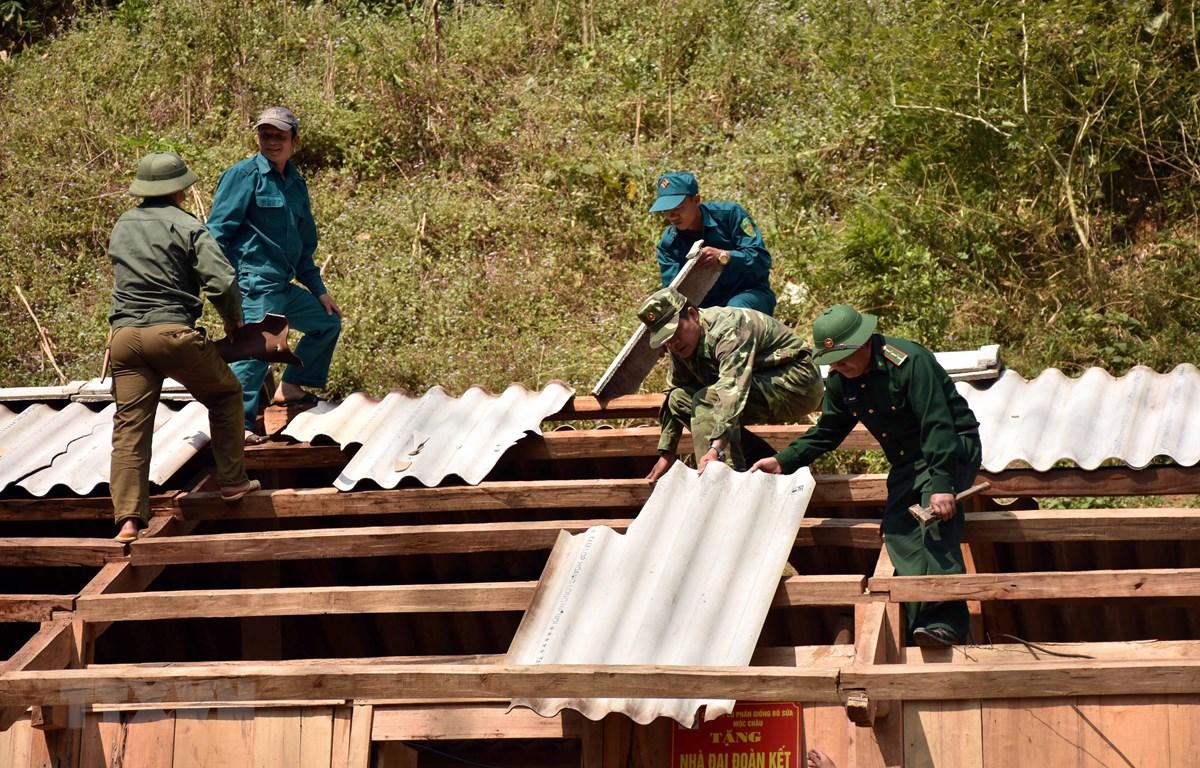 Cán bộ, chiến sỹ đồn biên phòng cửa khẩu Lóng Sập giúp người dân sửa lại nhà. (Ảnh minh họa: Hữu Quyết/TTXVN)