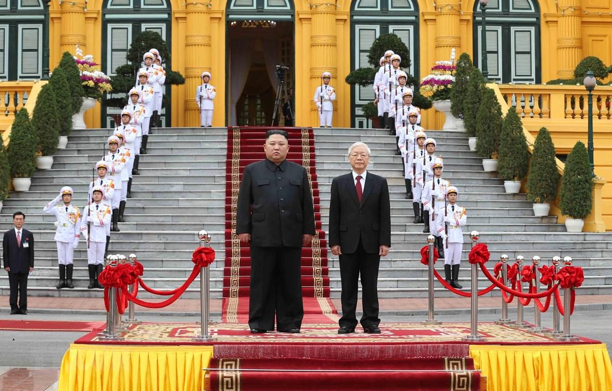 Tổng Bí thư, Chủ tịch nước Nguyễn Phú Trọng và Chủ tịch Triều Tiên Kim Jong-un trên bục danh dự, thực hiện nghi lễ chào cờ. (Ảnh: Trí Dũng/TTXVN)