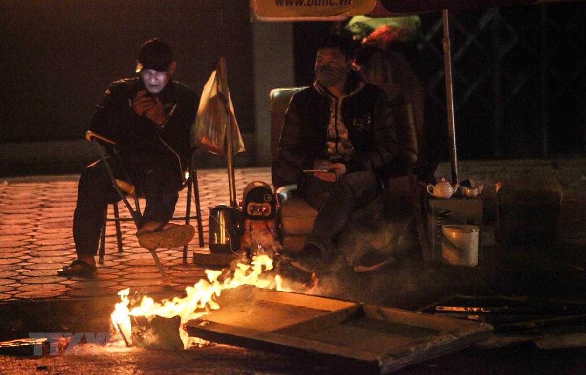Người dân lao động đốt lửa, chống lại cái lạnh trong đêm 28/12/2018 trên phố Hào Nam. (Ảnh: Minh Hoàng/TTXVN phát)