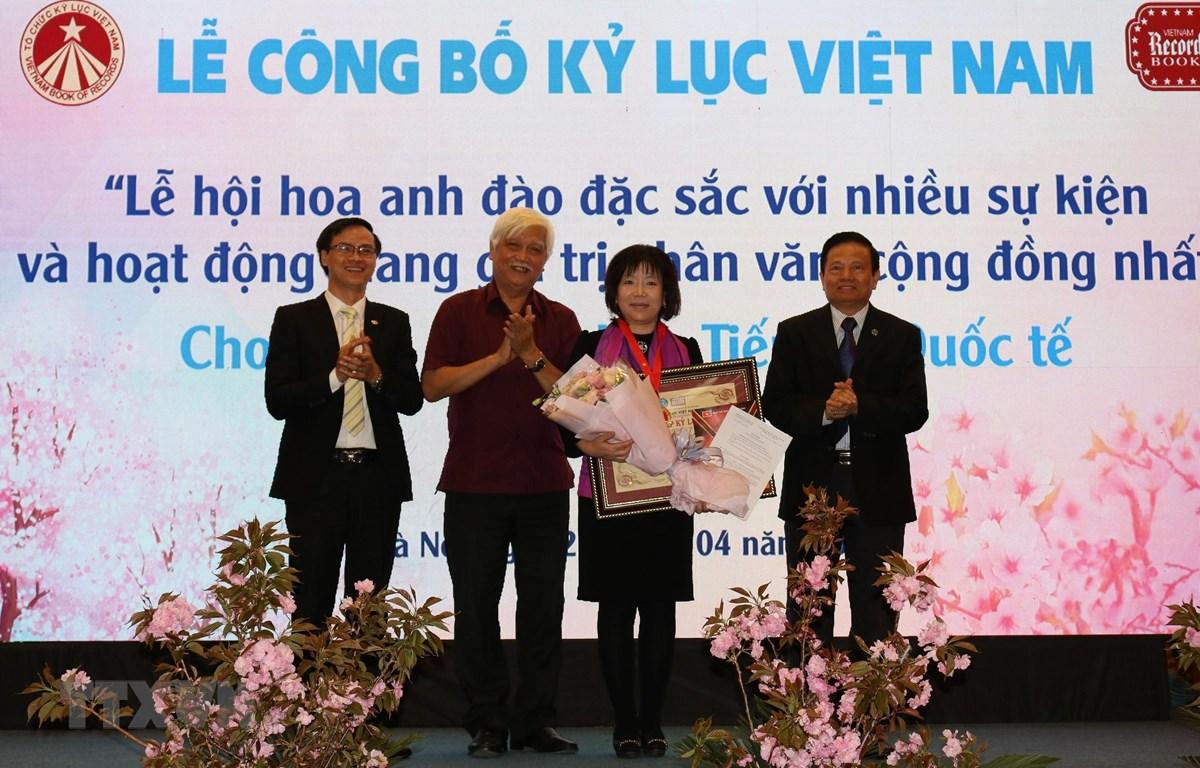 Trao bằng Kỷ lục Việt Nam 'Lễ Hội hoa anh đào đặc sắc với nhiều sự kiện và hoạt động mang giá trị nhân văn, cộng đồng nhất' cho Công ty Cổ phần Tiến bộ Quốc tế (AIC Group). (Ảnh: Nguyễn Thắng/TTXVN)
