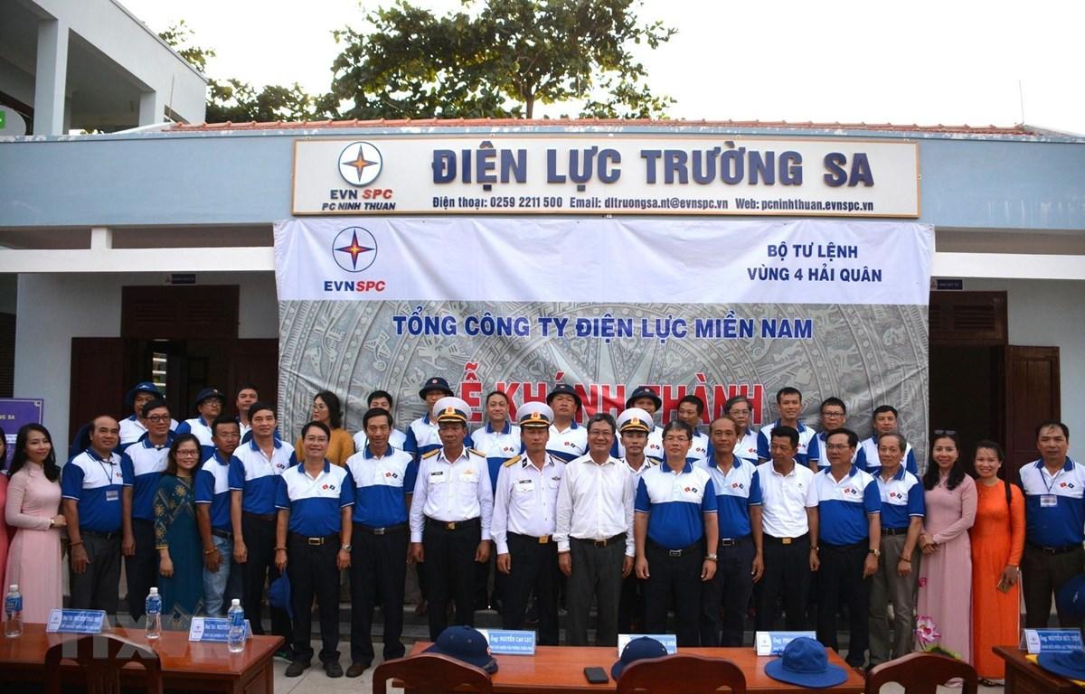 Đoàn công tác Tập đoàn Điện lực Việt Nam chụp ảnh lưu niệm trước trụ sở, văn phòng làm việc Điện lực Trường Sa. (Ảnh: TTXVN phát)