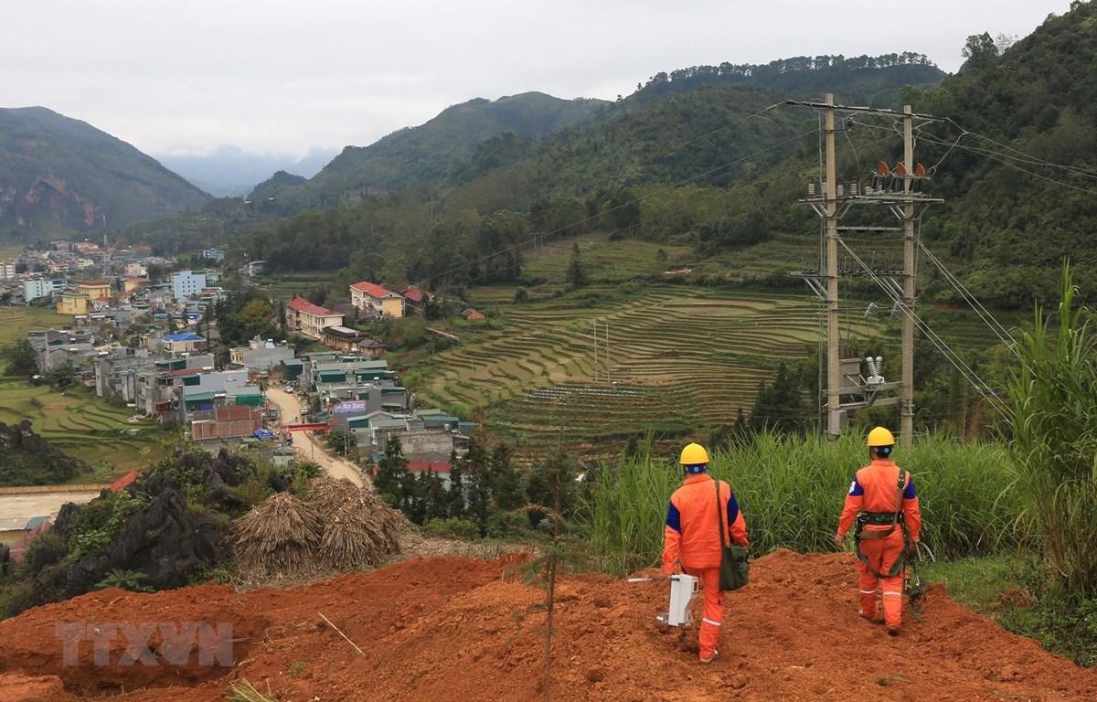 Công nhân Công ty Điện lực Hà Giang lắp đặt công tơ cho khách hàng trên địa bàn huyện Đồng Văn. (Ảnh: Ngọc Hà/TTXVN)