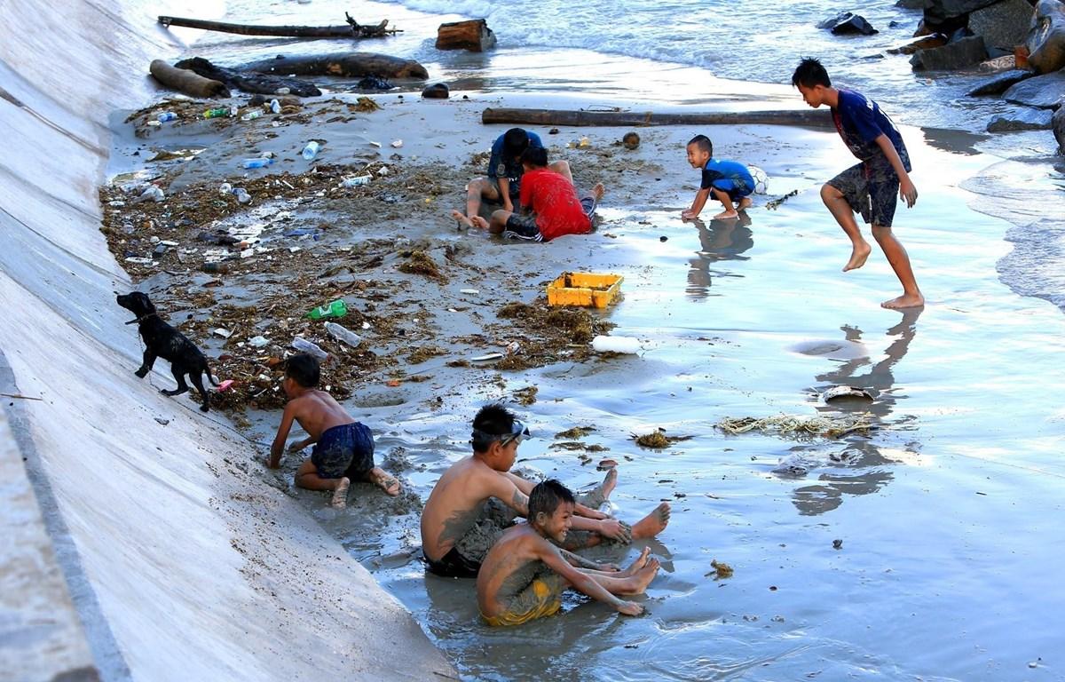 Những đứa trẻ chơi đùa cùng với rác tại bãi tắm gần Cầu Tàu 914. (Ảnh: Ngọc Hà/TTXVN)