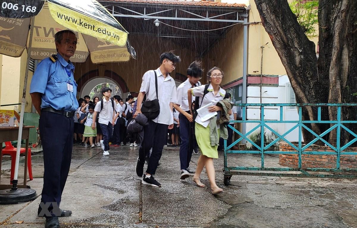 Mưa lớn khiến thí sinh gặp khó khăn khi rời khỏi điểm thi tại Hội đồng thi Trường THPT Marie Curie, Quận 3, Thành phố Hồ Chí Minh. (Ảnh: Xuân Dự/TTXVN)