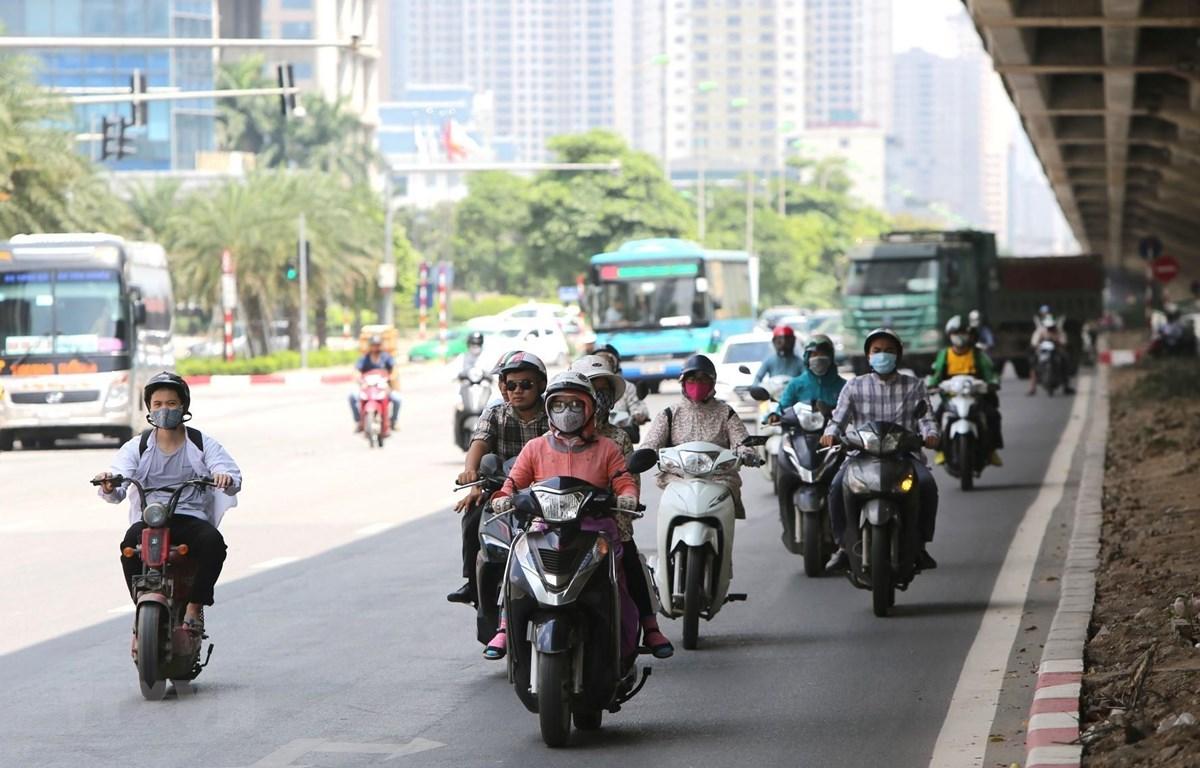 Người tham gia giao thông phải tránh nắng dưới bóng râm của gầm cầu trên tuyến đường Phạm Hùng. (Ảnh: Thành Đạt/TTXVN)