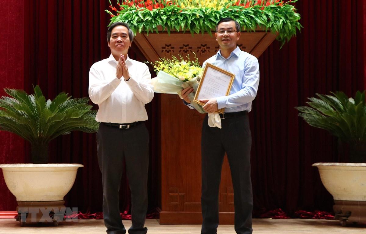 Đồng chí Nguyễn Văn Bình, Ủy viên Bộ Chính trị, Bí thư Trung ương Đảng, Trưởng Ban Kinh tế Trung ương trao Quyết định của Ban Bí thư cho đồng chí Ngô Văn Tuấn. (Ảnh: Nhan Sinh/TTXVN)