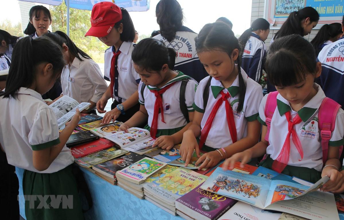 Học sinh huyện Quảng Điền tham quan triển lãm và đọc sách trong Ngày sách Việt Nam. (Ảnh: Hồ Cầu/TTXVN)