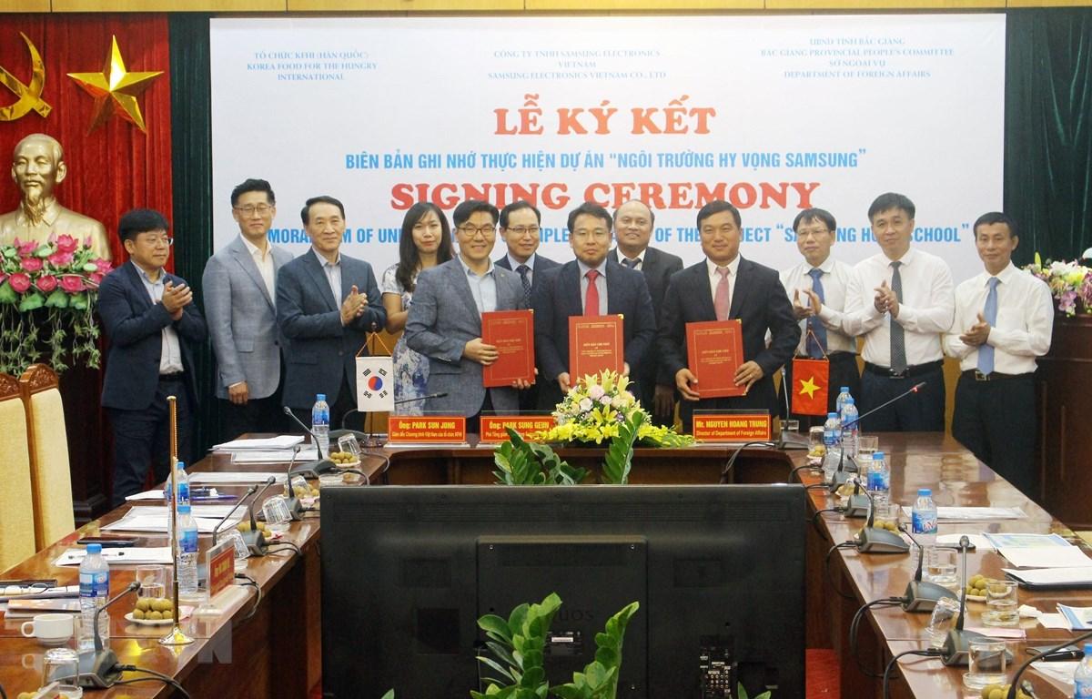 Đại diện UBND tỉnh Bắc Giang cùng đại diện công ty Samsung Việt Nam và tổ chức KFHI ký kết biên bản ghi nhớ dự án Trường học Hy vọng Samsung. (Ảnh: Tùng Lâm/TTXVN)