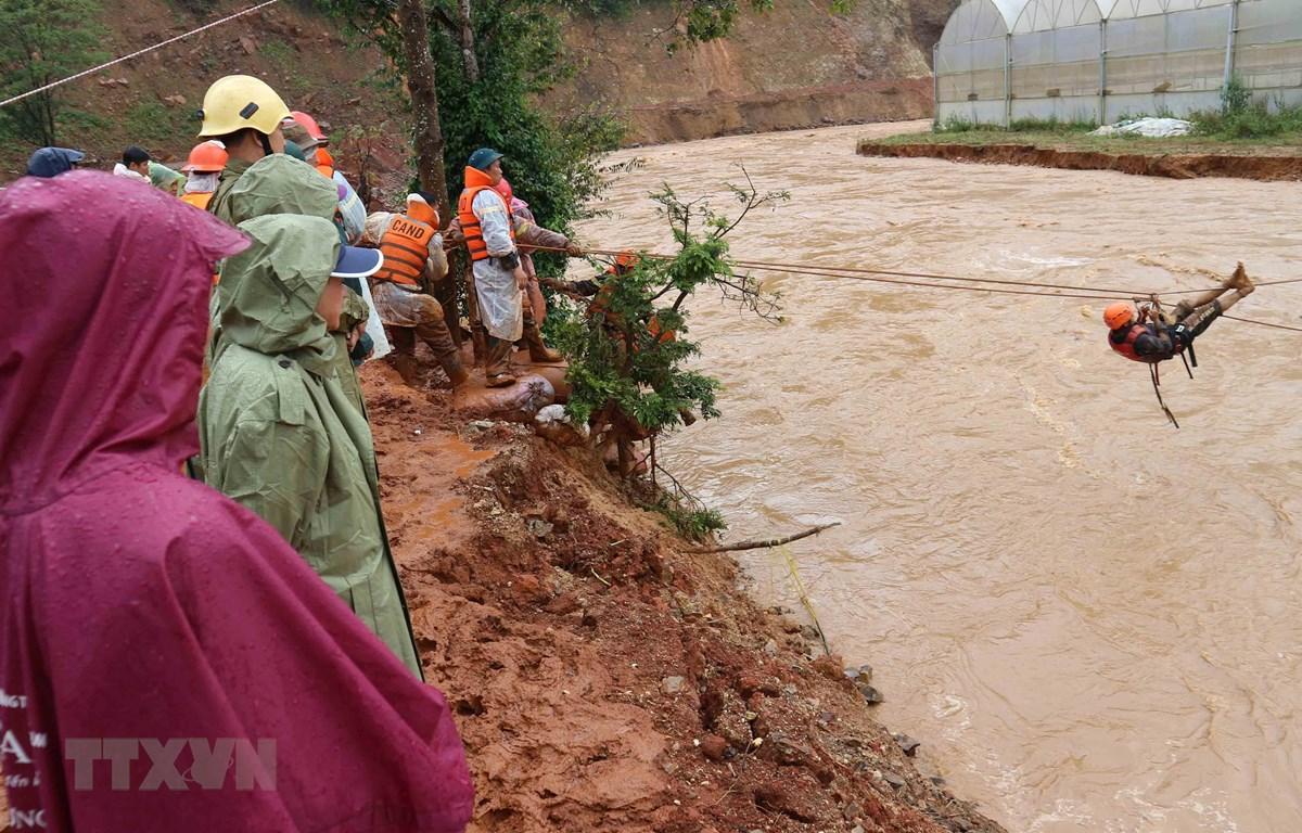 Một người dân bị mắc kẹt 'đu dây'qua dòng nước lũ nhờ sự hỗ trợ của lực lượng cứu hộ. (Ảnh: Nguyễn Dũng/TTXVN)