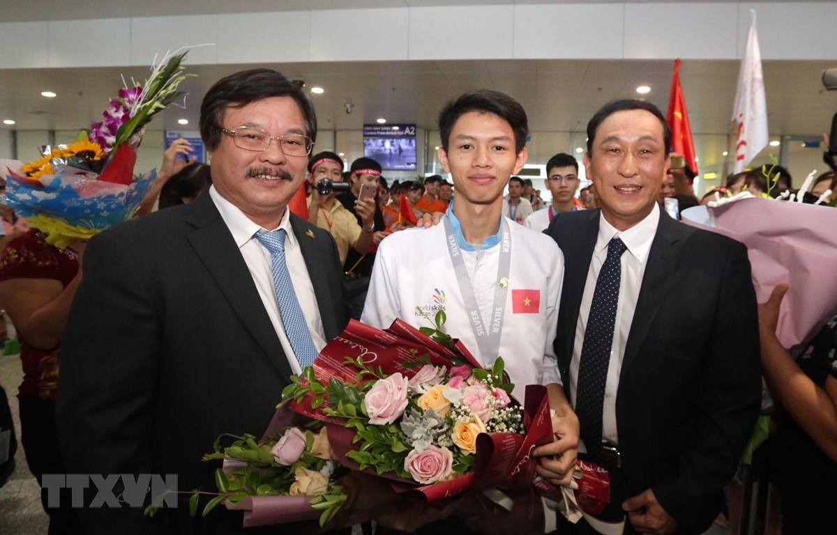 Tổng Cục trưởng Tổng cục Giáo dục nghề nghiệp Nguyễn Hồng Minh tặng hoa cho thí sinh Trương Thế Diệu đạt Huy chương Bạc Kỳ thi tay nghề thế giới lần thứ 45 nghề Phay CNC tại Sân bay quốc tế Nội Bài. (Ảnh: Anh Tuấn/TTXVN)