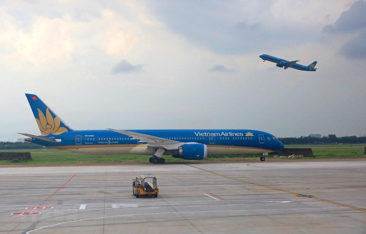 Máy bay của hãng hàng không Vietnam Airlines cất và hạ cánh tại sân bay Tân Sơn Nhất. (Ảnh: Ngọc Hà/TTXVN)